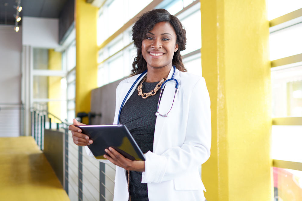 Portrait of a female doctor holding her patient chart on digital tablet in bright modern hospital-1