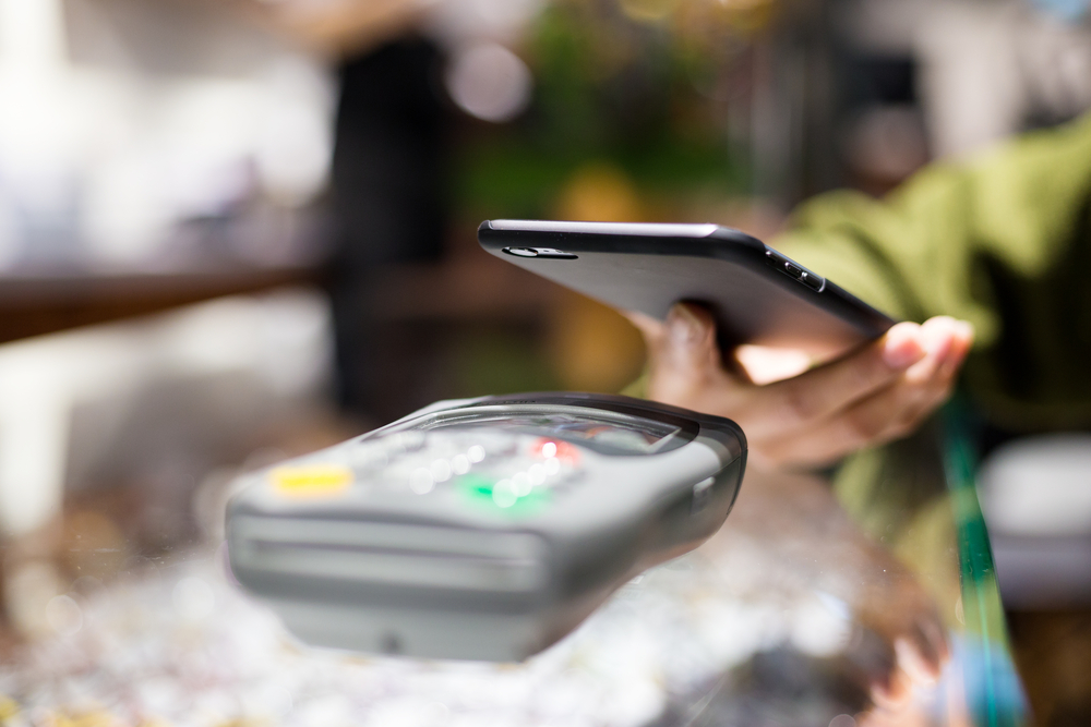 Woman paying with smartphone by NFC